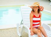Relaxed Young Woman In Hat Sitting On Sunbed And Looking On Copy