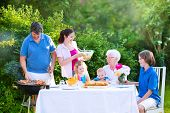 Happy grandmother enjoying sunny summer day having lunch with family