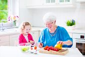Beautiful senior lady, happy loving grandmother making healthy salad for lunch with granddaughter
