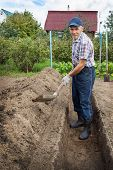 An Elderly Man Is Digging The Earth To Build A Deep Bed Of