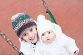 Brother And Baby Sister Swinging In A Park On A Cold Winter Day