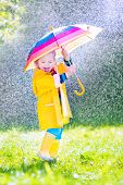 picture of coat  - Funny cute curly toddler girl wearing yellow waterproof coat and boots holding colorful umbrella playing in the garden by rain and sun weather on a warm autumn or sumemr day - JPG