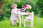 stock photo of girl toy  - Adorable toddler girl with curly hair wearing a colorful dress on her birthday playing tea party with a teddy bear doll toy dishes cup cakes and muffins in a sunny summer garden - JPG