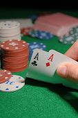 Chips and cards for poker in hand on green table