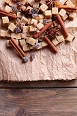 Brown sugar cubes and spices on paper background