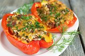 Stuffed red peppers with greens on plate on wooden table