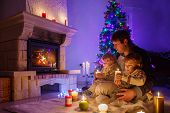 image of father time  - Young father and his two little children sitting by a fireplace at home on Christmas time