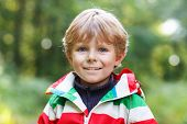Portrait Of Blond Little Preschool  Boy In Colorful Waterproof Raincoat In Autumn Forest