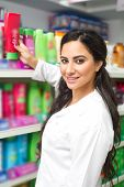 young woman holding bottle of shampoo in supermarket