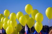 The Yellow Rubber Balloons Filled With Gas Against The Blue Sky.