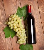 Red wine bottle and bunch of white grapes on wooden table background