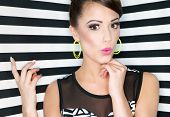 Attractive young surprised woman  on stripy background, pointing up, beauty and fashion concept