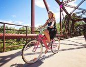 a pretty girl riding a bicycle across a bridge