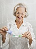 Smiling senior woman squeezing toothpaste on toothbrush in bathroom