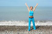 woman wearing sporty clothers with raised hands on sea coast