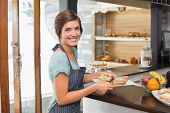 Pretty waitress holding plate of food at the coffee shop