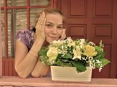 Young Smiling Girl On Porch With A Pot Of Bright Flowers