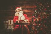 Santa Claus  with phone in wooden home interior