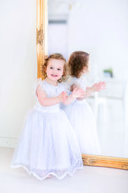 stock photo of toddlers tiaras  - Sweet curly little girl with big beautiful eyes iwearing a white bridesmaid dress sitting at a big window playing princess in a sunny living room - JPG