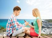 summer, vacation, technology, addiction and friendship concept - couple with smartphones sitting on bench over seashore background