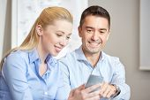 business, people, technology and teamwork concept - smiling businessman and businesswoman with smartphones meeting in office