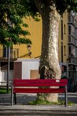 Red Park Bench In Urban Setting