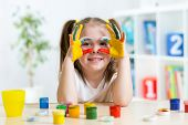 cute kid girl showing her hands painted in bright colors
