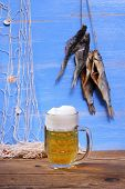 Beer On Blue Background With Dried Rudd Fish