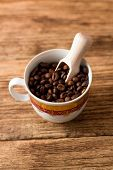 Upper View On Cup With Coffee Grains And Wooden Spoon