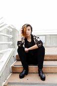 Slender Asian American Woman Sitting On Steps
