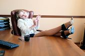image of secretary  - blonde secretary talking with phone at the office with legs on the table - JPG