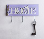 Old key hanging from hook, on light wall background
