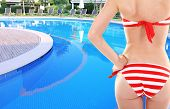 Young woman with slim body in swimsuit on swimming pool background