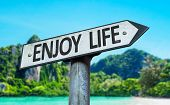 Enjoy Life sign with a beach on background