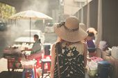 stock photo of southeast asian  - A young woman wearing a hat is walking in the streets of an asian country