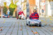 stock photo of little kids  - Two little kids in red jackets driving old vintage and race cars and making competition outdoors - JPG