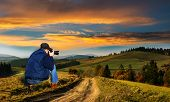 picture of asheville  - Man photographer in the mountains at sunset pictures of autumn landscape in front of him - JPG