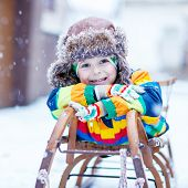 stock photo of snow-slide  - Cute little funny boy in colorful winter clothes sliding on snow sledge outdoors during snowfall - JPG