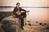stock photo of singer  - Freelance singer on tour is playing music on a sea coast - JPG