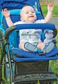 Happy baby waving from blue baby carriage