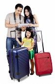 foto of carry-on luggage  - Cheerful family carrying luggage to holiday and looking an online map on the digital tablet - JPG