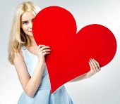 Young blonde beauty holding big heart