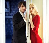 Attractive couple standing next to a white door