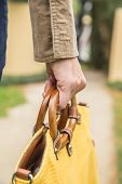 Woman hand holding yellow purse