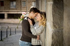 picture of urbanization  - candid portrait of beautiful European couple with rose in love kissing on street alley celebrating Valentines day with passion against stone wall on urban background - JPG