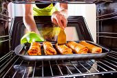 image of oven  - Housewife preparing cakes in the oven at home - JPG