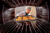 stock photo of oven  - Chef prepares pastries in the oven - JPG