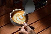 foto of latte  - Making of cafe latte art on the wooden table - JPG