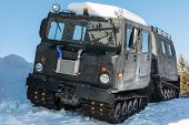stock photo of amphibious  - articulated military tracked cargo vehicle with two units on snow - JPG