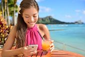 picture of waikiki  - Woman using smartphone at beach bar drinking Mai tai Hawaiian cocktails having fun - JPG